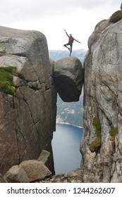 Young woman balancing on one leg on Kjerag bolten in Norway on a cloudy day of summer