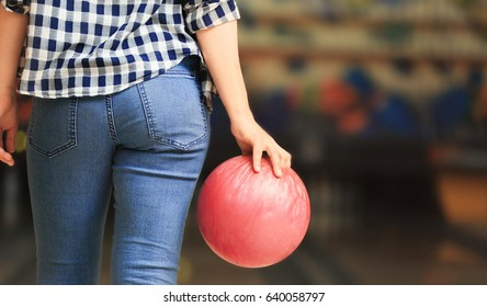 Young woman with ball in bowling club, closeup