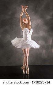 Young woman ballerina in white tutu, dancing on pointe with arms overhead, in the studio against a dark background.