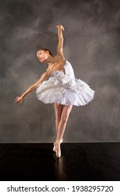 Young woman ballerina in white tutu, dancing on pointe while leaning right, in the studio against a dark background.