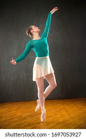 Young woman ballet dancer in a green leotard with tan skirt, dancing on pointe in a studio shot, against a gray background.