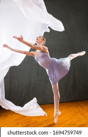 Young woman ballet dancer in a lavender dress, dancing on pointe with floating white fabric in a studio shot, against a gray background.