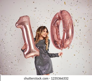 "Young woman with balloons building the figure ""10"""