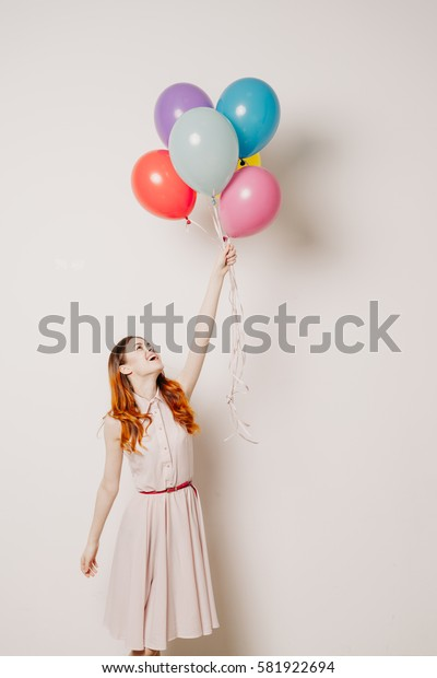 Young woman with balloons smiling and flies on balls, light background