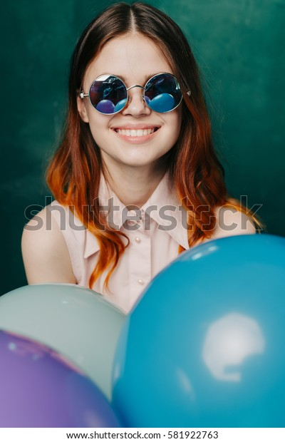 Young woman with balloons smiling and looking at the camera