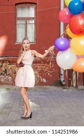Young woman with balloons, urban scene, outdoors