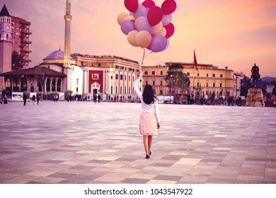 Young woman with a lot of balloons walking in Tirana central square in evening dreamy scenic sunset