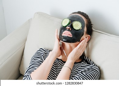 Young woman with bamboo charcoal peel off facial mask. Sitting in a couch at home, leaning her back. Hair in a bun. Cucumber slices over her eyes. Listening to the music.