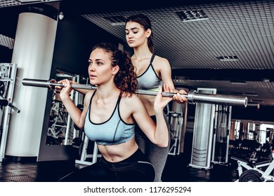 Young woman with barbell flexing muscles and making shoulder press squat in gym.
