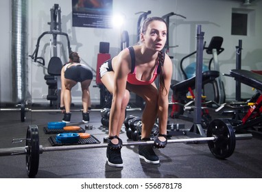 young woman with a barbell in the gym