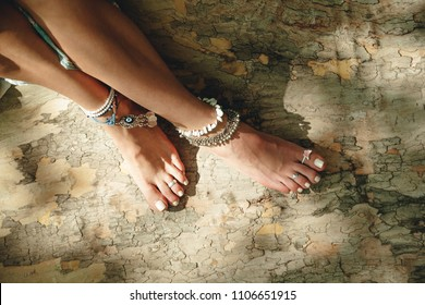young woman bare feet on tree surface with boho style jewelry anklets and toe rings summer day oitdoor