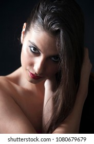 Young woman, bare shoulders, playing with her black hair, sensual eyes