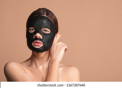 Young woman with bare shoulders standing isolated on the beige background and having a black moisturizing mask on her face. Copy space on the right side