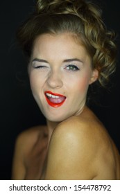 A young woman with bare shoulders winks on a dark background