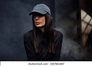 Young woman in baseball cap wearing black in front of black back ground - low-light portrait in dark.