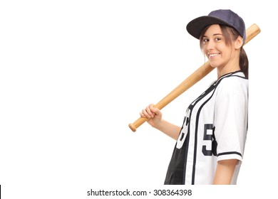 Young woman in a baseball jersey, holding a baseball bat and leaning against a wall isolated on white background