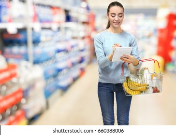 Young woman with basket checking shopping list in notebook at supermarket