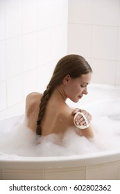 Young woman in bath tub, scrubbing shoulder