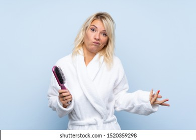 Young woman in a bathrobe with hair comb making doubts gesture while lifting the shoulders