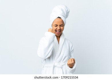 Young woman in bathrobe over isolated white background celebrating a victory