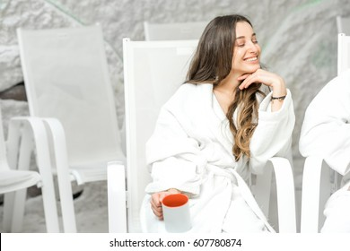 Young woman in bathrobe relaxing with tea cup in the salt room. Applying salt therapy in the Spa