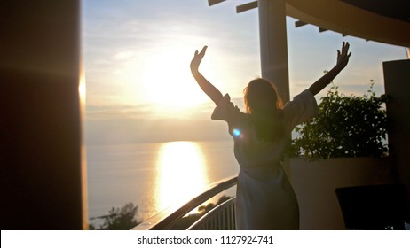 Young woman in bathrobe stretching arms on terrace in the morninig during amazing sunrise enjoying the moment with beautiful sea view