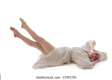 Young woman in bathrobe and towel lying