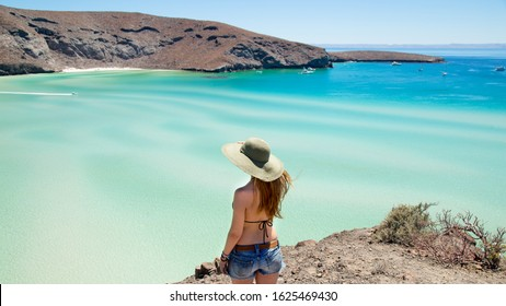 Young woman with a beach hat admiring the beautiful view of the Balandra Beach from the top of the cliff.