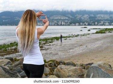 Young woman at the beach of Stanley Park looking at Vancouver in the hill side and framing the view with hands trying to imagine a nice place to live. Vancouver, British Columbia, Canada.