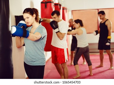 young woman  beating boxing bag training in boxing gloves