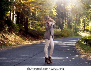 Young woman in beautiful autumn staying on street
