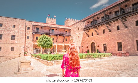 A young woman in a beautiful dress in front of the medieval castle in Siguenza, Guadalajara in Castilla-la-Mancha region of Spain near Madrid. Beautiful, old and medieval castle in Spain