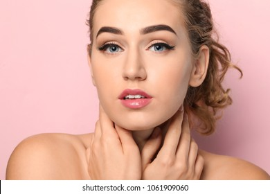 Young woman with beautiful eyebrows on color background, closeup