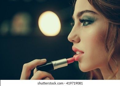 Young woman with beautiful face doing makeup with lipstick in beauty salon