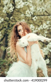 Young woman with beautiful face and long curly hair in glamour dress holding cute white small goat in lush blooming garden