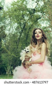 Young woman with beautiful face and long curly hair in glamour pink dress showing tongue holding cute small dog outdoor with green trees