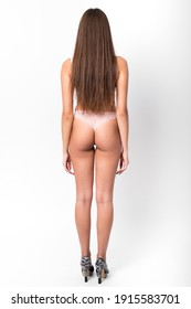 A young woman with a beautiful fit body in underwear stands in the studio with her back on a white background