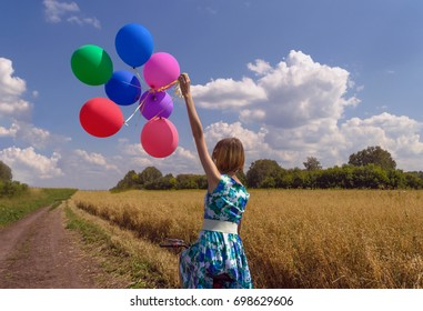 young woman in beautiful floral dress on bicycle with colorful balloons in the oat field representing happiness and freedom