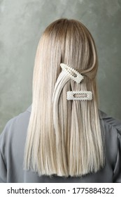 Young woman with beautiful hair clips on grey background, back view