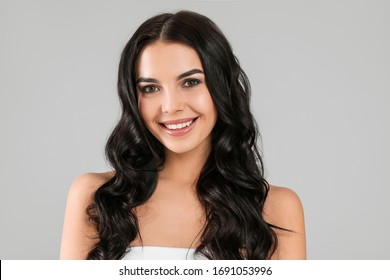 Young woman with beautiful healthy hair on grey background