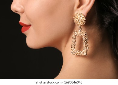 Young woman with beautiful jewelry on dark background, closeup