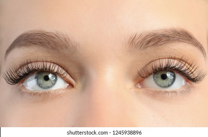 Young woman with beautiful long eyelashes, closeup. Extension procedure