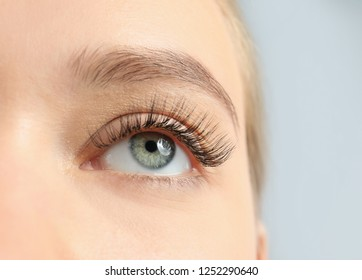 Young woman with beautiful long eyelashes on gray background, closeup. Extension procedure