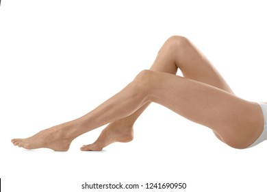 Young woman with beautiful long legs on white background, closeup