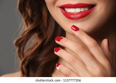 Young woman with beautiful manicure on grey background, closeup