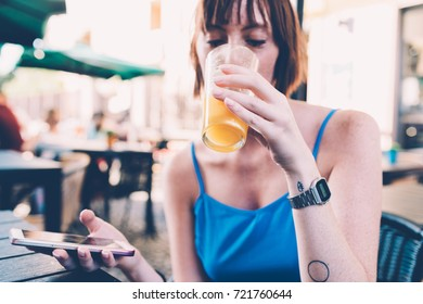 young woman beautiful outdoor drinking juice using smart phone sitting bar - technology, hapy hour, refreshing concept