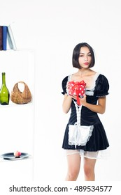 Young woman with beautiful serious face brunette in black sexy housemaid uniform holding red present box posing on white shelves with kitchenware background isolated