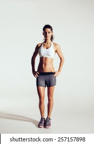Young woman with beautiful slim healthy body posing in studio. Fitness female model in sportswear on grey background