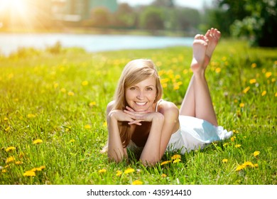Young woman with a beautiful smile with healthy teeth with flowers. Face of a beautiful positive girl  Concept on the subject of dentistry, stomatology, dental care.