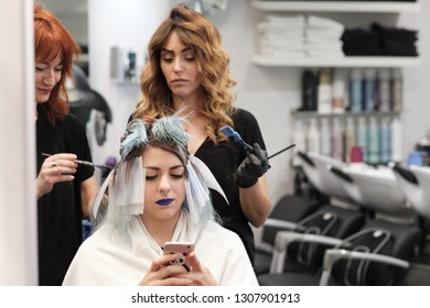 A young woman at the beauty salon with a blue tint on her hair